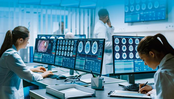 Trabajadores utilizando pantallas para analizar casos clínicos
