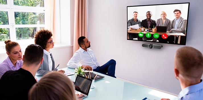 Oficinistas asistiendo a una conferencia con sistemas de vídeo