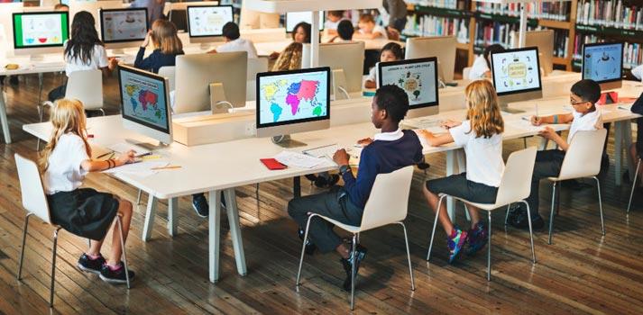 Estudiantes en un aula trabajando con ordenadores