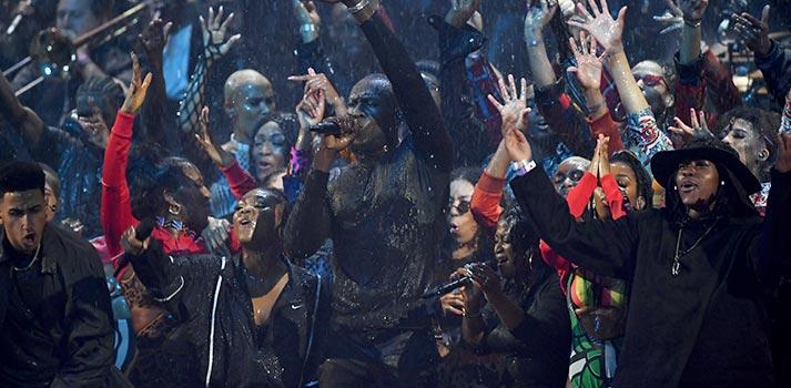 Rapero Stormzy cantando bajo la lluvia con micrófonos Sennheiser en los Brit Awards